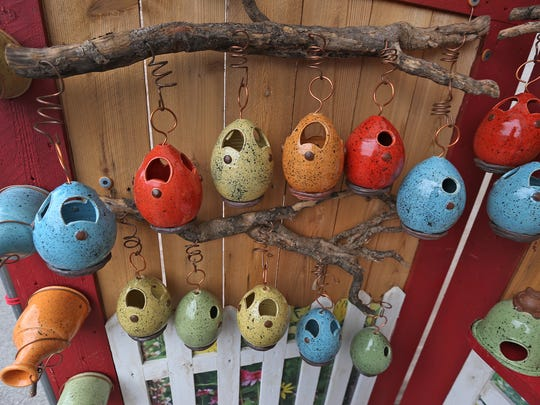 Bird feeders and houses, and toad houses, are creatively displayed at the Debbie's Birdhouses booth at the Talbot Street Art Fair, Sunday, June 14, 2015.