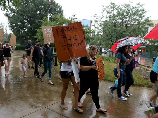 About 60 people marched in the rain after attending