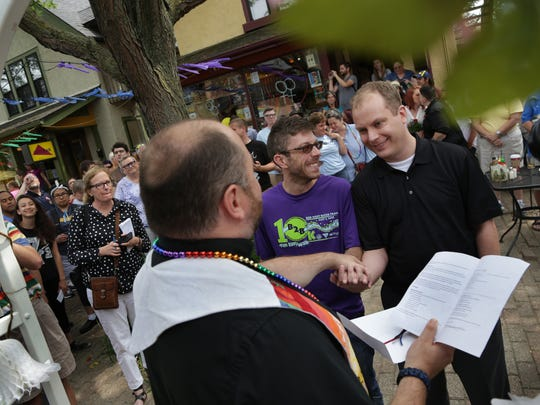 Chris Berghuis, 36, right and Derek Davis, 36 of Ann Arbor exchange vows in front of  the Reverend Greg Briggs  in Ann Arbor on Friday, June 26, 2015.