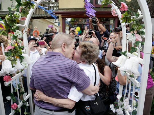 Ann Sorrell, 78, left, kisses Marge Eide, 77, as they are wed in Ann Arbor.