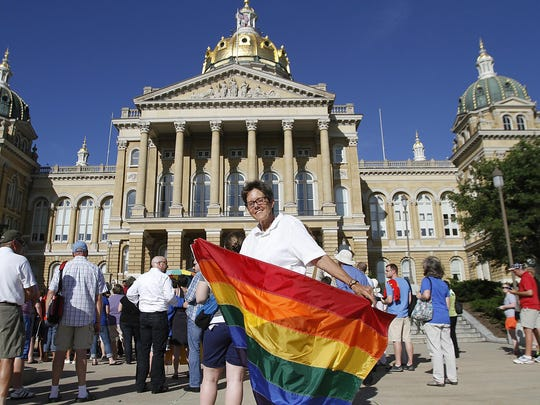 Sumitra Red Wing carries a rainbow flag in front of the Iowa Capitol building in this file photo.