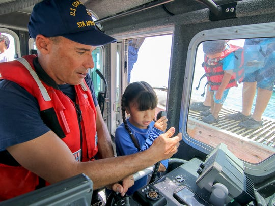 """Petty Officer Michael Genereux assists Hazel Huffer, 6, as they conduct a """"radio check"""" aboard the U.S. Coast Guard's response boat at the Merizo Pier on June 28. Virgilio Valencia/For Pacific Daily News"""