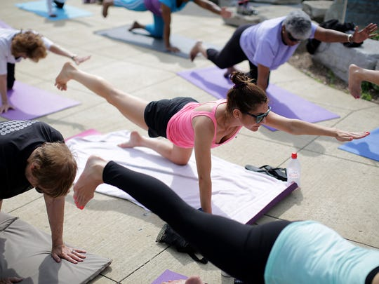 Sara Vollmer, 35, of Hoboken, N.J., reaches out with her left hand for the balancing table pose, during the Yoga on the Riverfront class lead by Michelle Moten, of Urban Solace studio in the wetland area of Milliken State Park in Detroit on Friday, June 26, 2015. The classes are free and sponsored by Blue Cross Blue Shield and the Detroit Riverfront Conservancy.