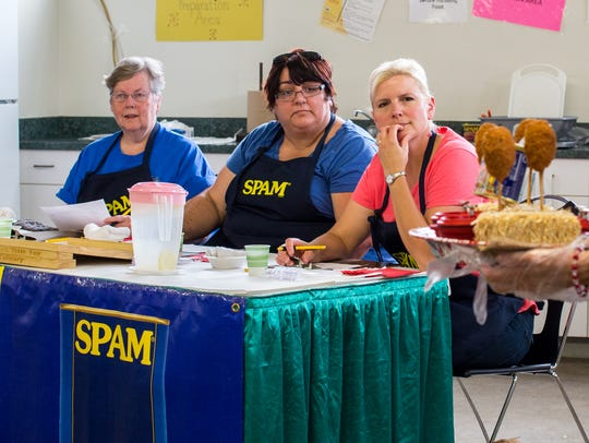 Spamcakes are presented to the crowd before being sampled