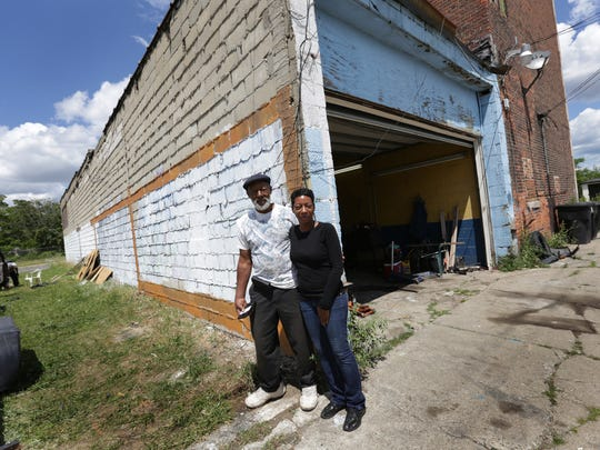 Roosevelt Hendrix, left, and his daughter Stacy Hendrix, both of Detroit  stand by the side of his building that he painted after getting a warning and ticket for having graffiti on Mack Avenue in Detroit on Wednesday, Aug. 5, 2015.