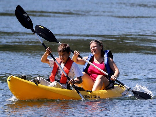 Erick Alvarez, 14, and his mother, Doris Alvarez, 42, both of Monmouth, finish second in the Great Willamette River Raft Race at Wallace Marine Park in Salem on Saturday, Aug. 8, 2015.
