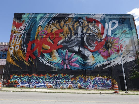 """Rise Up,"" a mural by Meggs, on Russell Street on July 30, 2015. Meggs incorporated existing art (on the bottom of the wall) into his piece."