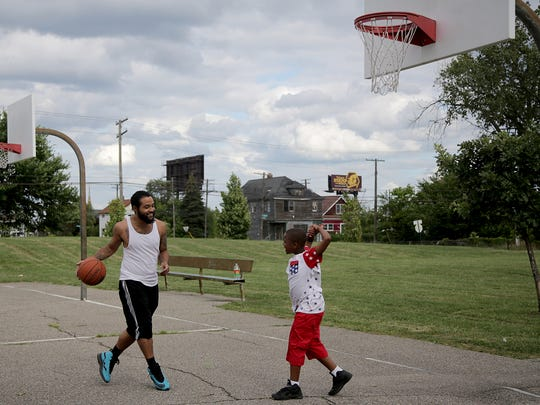 Dion Morris, 25, of Detroit plays basketball with DeJuan Larry, 7, of Detroit at Bradby Park in Detroit on Thursday, Aug. 20, 2015.
