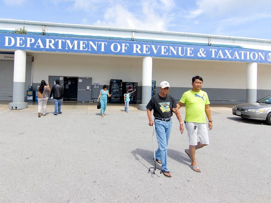Residents enter and exit the Department of Revenue and Taxation building in Barrigada in this file photo.