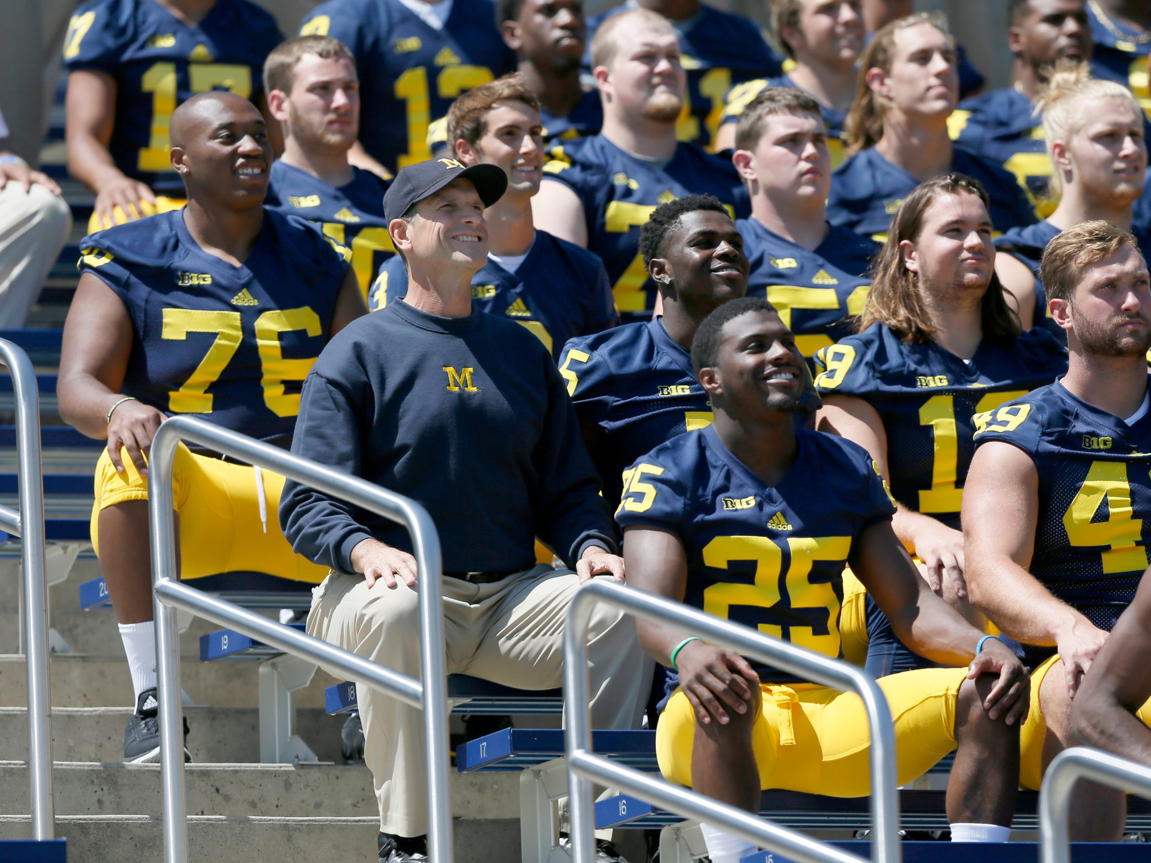 Michigan head coach Jim Harbaugh, left center, takes his seat off to the side with his players during the team's official photo at Michigan Stadium during football media day on August 6, 2015, in Ann Arbor.