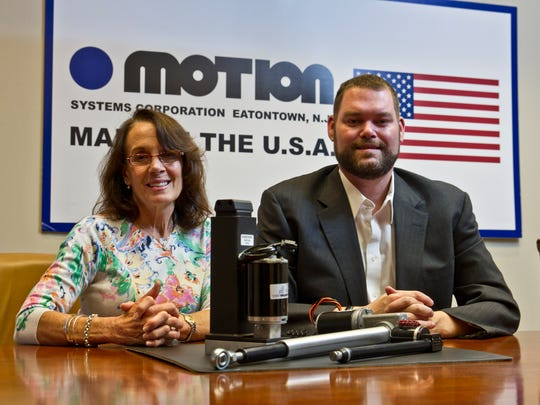 Motion Systems is a family-owned manufacturer of custom electromechanical linear actuators. Controller Kathleen Ryan and CEO Erik Wolf pose with an actuator in the Eatontown headquarters.