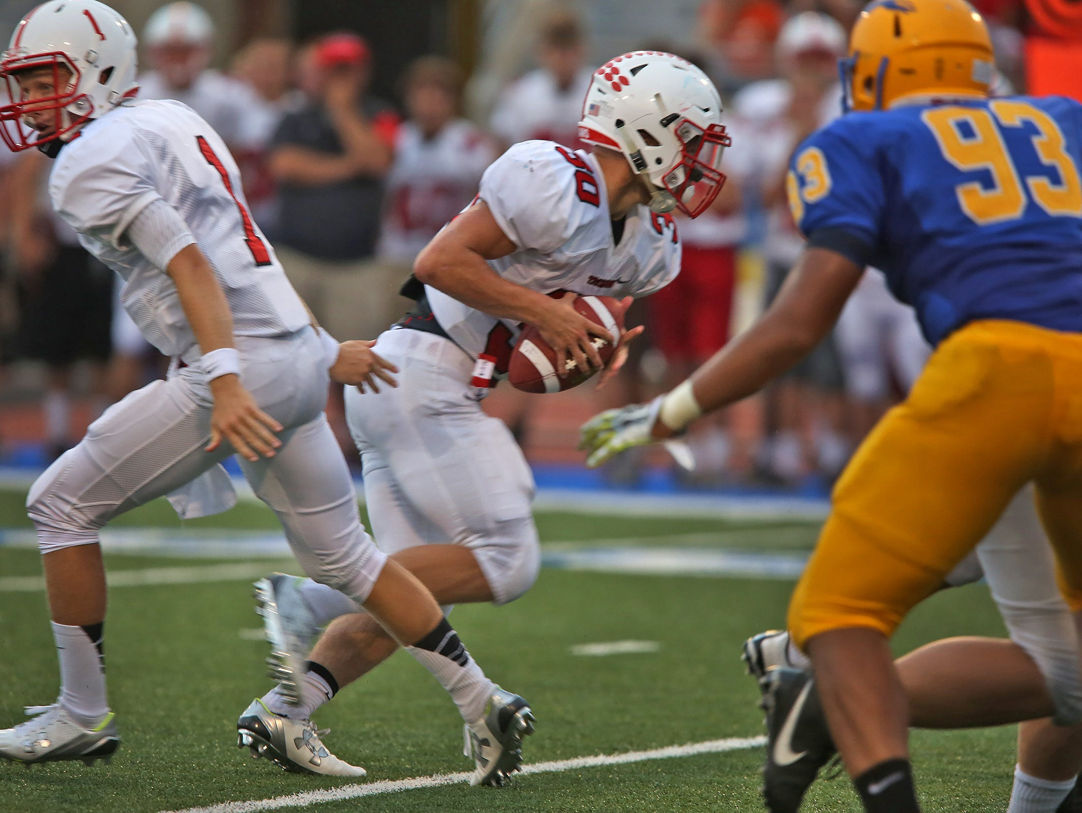 Center Grove quarterback #1 Joey Siderewicz passes to #30 Titus McCoy during the Center Grove at Carmel High School football game, Friday, September 4, 2015. Center Grove won 24-21.