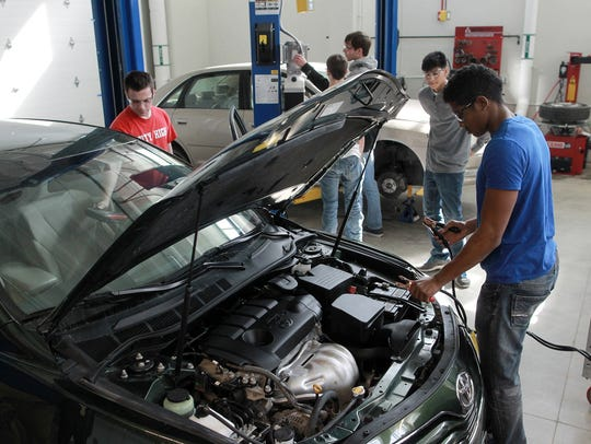 Ali Omar, 18, works on a car at the auto shop at the
