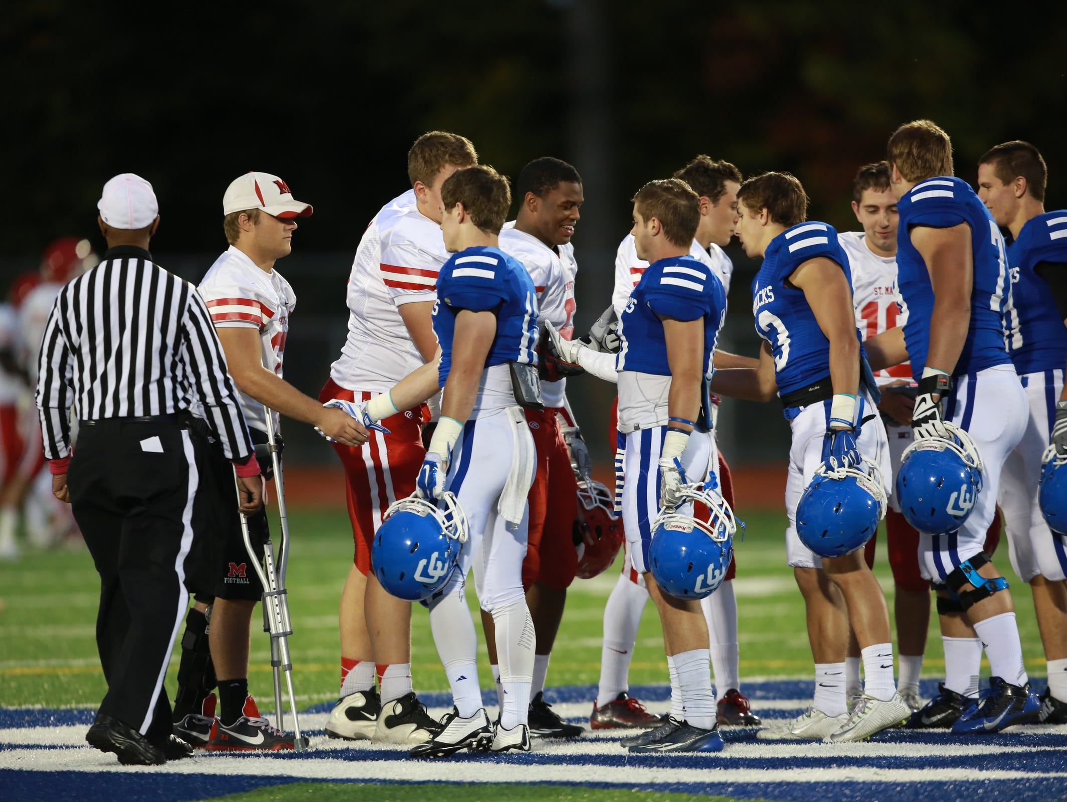 Orchard Lake St. Mary's at Novi Detroit Catholic Central shake hands before the start of their game in Novi, Mich. on Friday, Oct. 9, 2015.