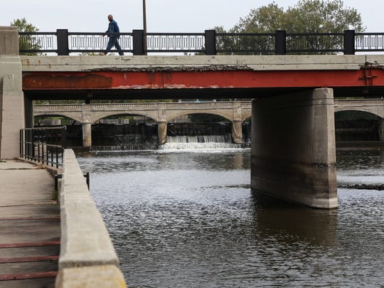 A man crosses a bridge over the Flint River near the Hamilton Dam in downtown Flint on Thursday, Oct. 8, 2015,