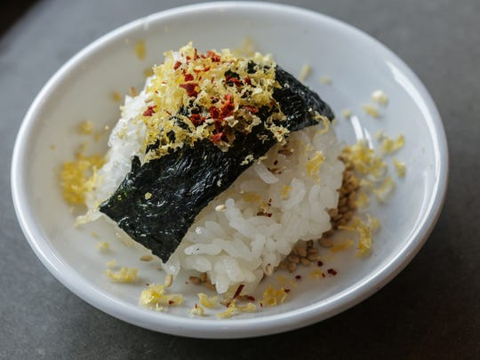 Onigiri, a sushi rice bowl with a strip of nori, shaved duck egg yolk, Korean chili flakes and smoked soy sauce, is served during the Detroit Free Press Top 10 Takeover dining series at Johnny Noodle King in downtown Detroit on Oct. 12, 2015.