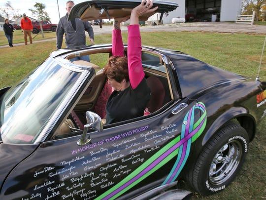 Jennifer Barnett takes off the t-top of her special 1974 Corvette.