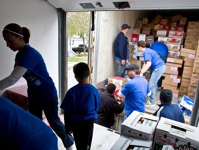 Volunteers unload a large load of donated food. Volunteers