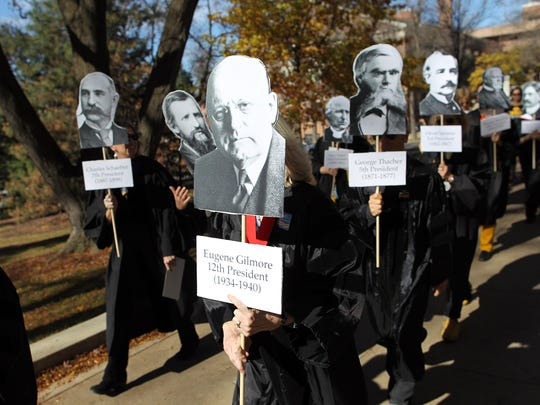 Protesters dressed as former University of Iowa presidents march along the Pentacrest on Monday, Nov. 2, 2015.
