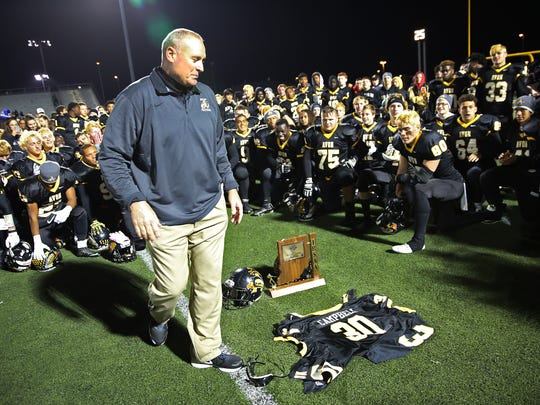 Avon head football coach Mark Bless looks at injured player Scott Campbell's jersey that players held up after the team victory, Oct.30, 2015.
