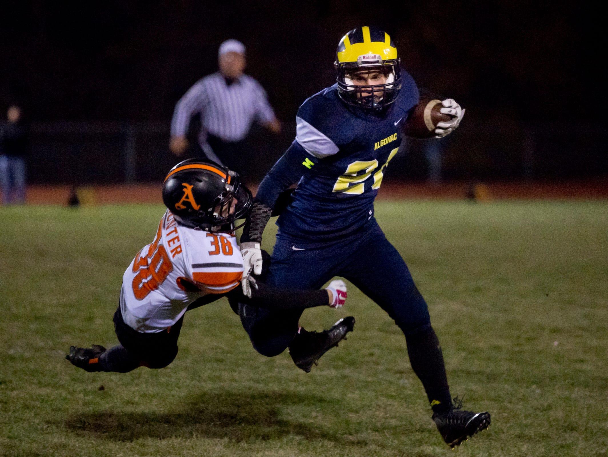 Algonac's Joe McKee runs the ball and breaks a tackle by Almont's Nathan Hunter during a football game Friday, November 6, 2015 at Algonac High School.