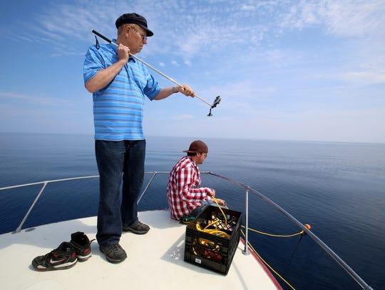 Shipwreck hunter David Trotter, left, uses his GoPro