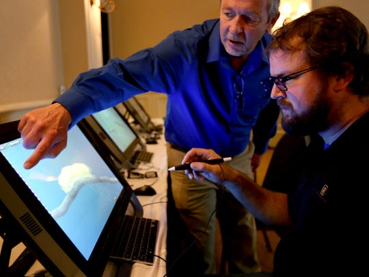 Ron Kiser, left, a director of sales with zSpace, helps Michael Woolworth, of Portland, learn to use a desktop version of virtual reality technology during a presentation for Oregon educators about the possibilities of virtual reality technology in classrooms at the Grand Hotel in Salem on Monday, Nov. 9, 2015.