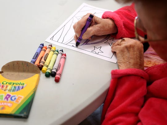Corki Miller colors at Among Friends Adult Day Respite Program at Center 50+. Coloring brings the participants a sense of peace and pride.