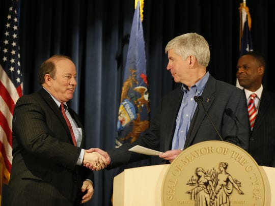 Detroit Mayor Mike Duggan, left, accepts a check from Michigan Governor Rick Snyder, as outgoing Detroit emergency manager Kevyn Orr, back right, watches during Press conference to announce the City of Detroit's exit from bankruptcy at the Public Safety Headquarters in Detroit on Wednesday, December 10,2014.
