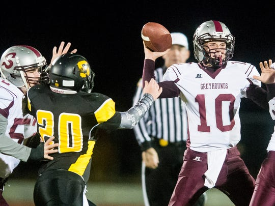 Shippensburg quarterback Tyler Gustafson (10) drops back to pass in front of Solanco's Gary Doubts on in a District 3 Class AAA playoff on Friday night. Gustafson struggled to throw in the high winds, and the Greyhounds lost, 43-0.