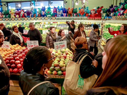 Shoppers are introduced to fresh produce for sale during the Green Grocer Project grocery store crawl at Honey Bee Market in southwest Detroit on Saturday, Nov. 14, 2015.