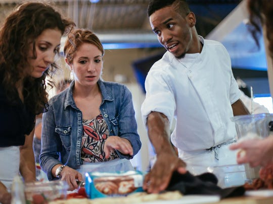 (Right to left) Greektown Casino Executive Sous Chef Rashad Patrick helps Plante Moran marketing members Julie Sherwood and Michelle Welsh during a food challenge for marketing team members at Great Lakes Culinary Center in Southfield on Wednesday Aug. 19, 2015.