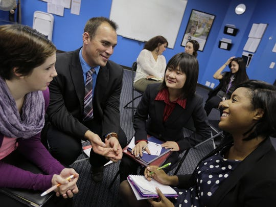 Christina Meyer, from left Matthew Bizoe, Mo Yang and Courtney Standiferat talk about the possible answers during a trivia quiz at Detroit Business Consulting, Inc. in Troy on Oct. 21, 2014.