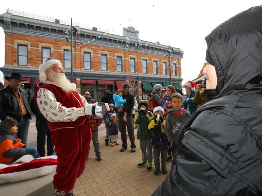 Santa Claus plays his concertina in front of a crowd of families during his arrival in Old Town Fort Collins on Saturday, Nov. 21. Kids can visit Santa from Noon to 6 p.m., Wednesday through Sunday until Dec. 13. From Dec. 14 through Christmas Eve, Santa's workshop will be open daily from Noon to 6 p.m.