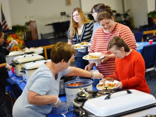 Laura Offutt, right, and caregiver Wendy Grove are served by Trail Church of the Nazarene member Allyann Palmer at the buffet line during a free Thanksgiving dinner at the New Freedom church on Thursday, Nov. 26, 2015.