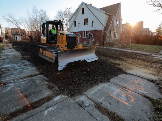 Workers back fill and work on the final grading of a lot next to an abandoned house in Detroit in 2014.