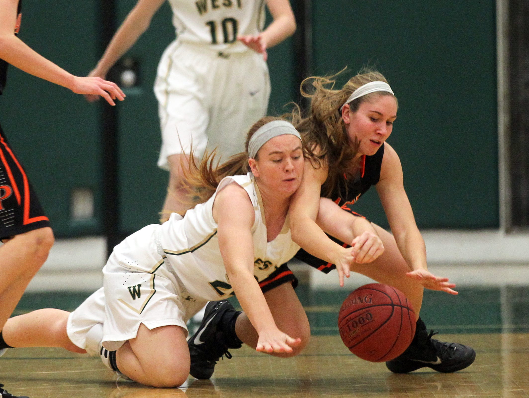 West High's Jessie Harder and Cedar Rapids Prairie's Taylor Moenk fight for the ball during their game on Tuesday, Dec. 1, 2015.
