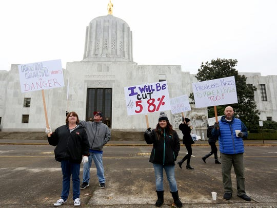 Karen Pearce, an Aumsville adult foster care provider, from left, her husband Scott Ludviksen, Teri Petre, a Salem adult foster care provider, Dakota Gibson, of Salem, and Robert Wicklund, a Salem adult foster care resident, protest a contract negotiated on their behalf by SEIU that they say will cut providers' reimbursement for caring for mental health clients by up to 60 percent at the Oregon State Capitol in Salem on Tuesday, Dec. 1, 2015.