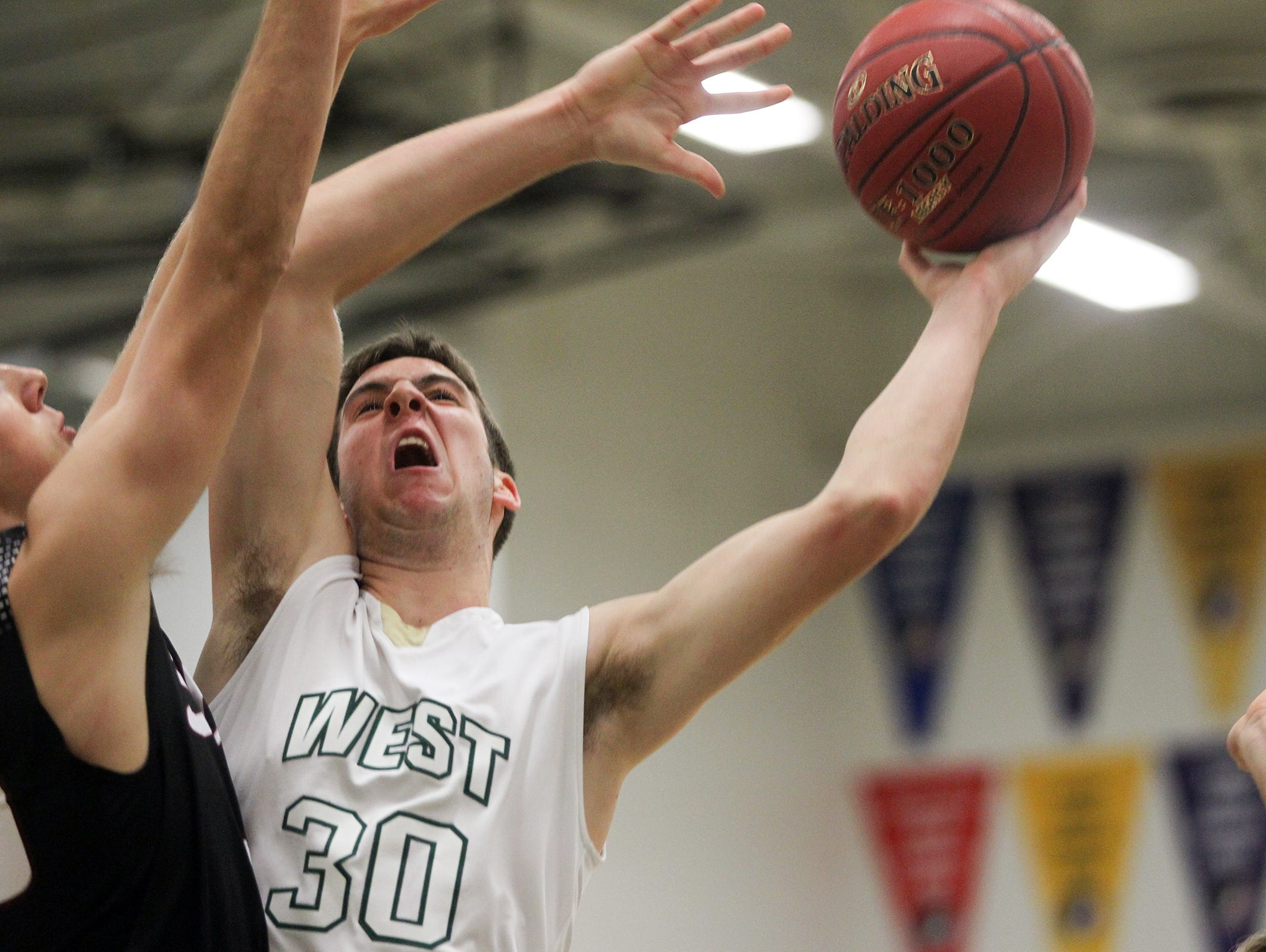 West High's Connor McCaffery goes up for a shot during the Trojans' game against Mount Vernon on Thursday, Dec. 3, 2015.
