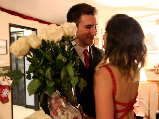 Aaron Opgenorth, a sophomore at South Salem High School, greets his girlfriend, Gaby Lacy, a junior at South Salem High School, with roses at her home before attending SnoBall on Saturday, Dec. 5, 2015.