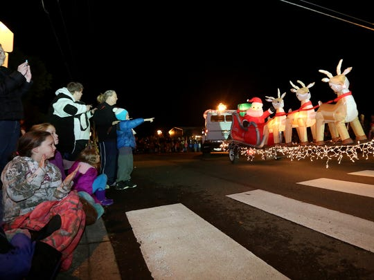 People line the road to see the fifth annual Sublimity Light Parade in Sublimity, Ore., on Saturday, Dec. 5, 2015.