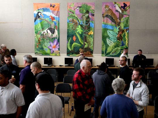 People gather for an art show featuring three painted banners at the Hillcrest Youth Correctional Facility in Salem on Wednesday, Dec. 9, 2015.