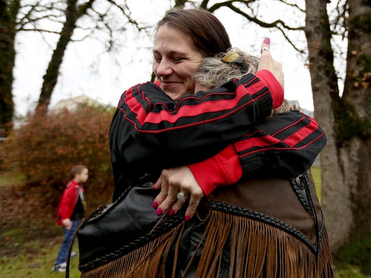 Koralee Norwood (facing), a mother and resident of Her Place, a transitional home in Salem, hugs Colleen Crook, the organizer of the sixth annual Salem Bikers Gone Wild Toy Run, during a toy delivery at the home on Saturday, Dec. 12, 2015.