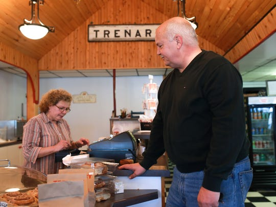 Tom Sluth, 58 of Saginaw stops in to pick up bags of Trenary Toast as cashier Yolanda Grainger rings up his order on Tuesday Nov. 17, 2015 at the Trenary Toast Cafe in Trenary.