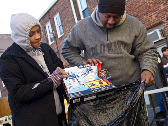 Nicole Andrews and Malachi Gary, both of Asbury Park, look over toys the received for their son Malachi Andrews Jr. The Asbury Park Toy Drive takes over a vacant storefront in downtown Asbury Park as hundreds of people line up for gifts, clothing, and food.