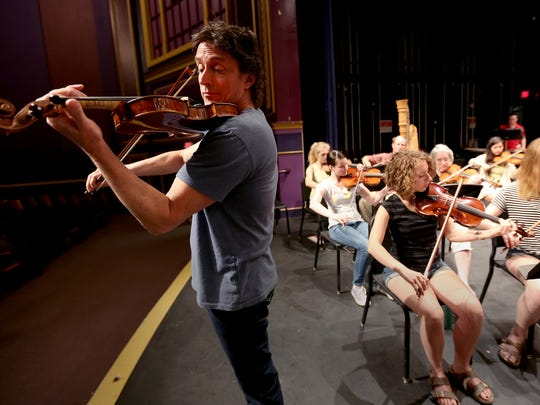 Salem native Peter Frajola, left, rehearses with Salem Youth Symphony at North Salem High School. Frajola was the guest violin soloist for the Salem Youth Symphony's 60th anniversary concert in May 2015.