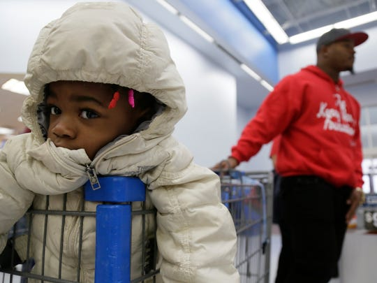 Carmen Brewer, 2, waits patiently as former Michigan football linebacker Kenny Demens, who plays for the NFL's Arizona Cardinals, is having his foundation, take people shopping at the Troy Walmart for the holidays Wednesday Dec. 23, 2015.