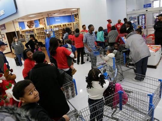 Families wait as Former Michigan football linebacker Kenny Demens, who plays for the NFL's Arizona Cardinals, is having his foundation take them shopping at the Troy Walmart for the holidays Wednesday Dec. 23, 2015.