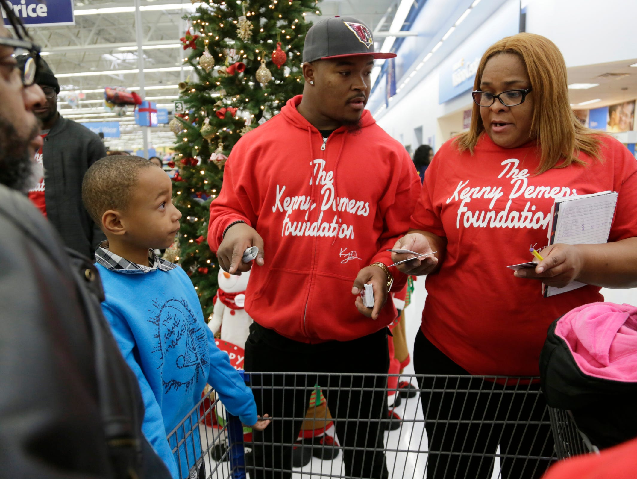 Former Michigan football linebacker Kenny Demens, left and his mom Tammy Demens, 47, of Oak Park prepare to hand out gift cards. Demens who now plays for the NFL's Arizona Cardinals, is having his foundation, take people shopping at the Troy Walmart for the holidays Wednesday Dec. 23, 2015.