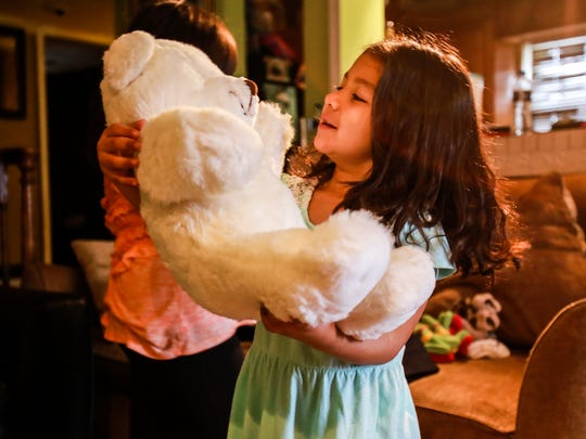 Joslyn Perez, 5, holds the teddy bear she receives